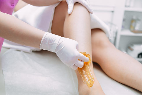 Young woman depilating legs with liquid