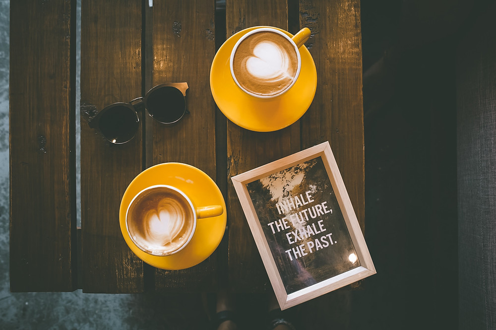 "Two lattes in yellow cups sit on a wooden table alongside a pair of sunglasses and a frame which reads ""inhale the future, exhale the past."" Photo by Toa Heftiba on Unsplash"