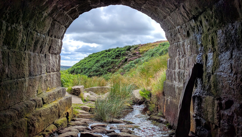 A stone tunnel in the foreground ends to show green hills in the background. Photo is courtesy of Eryk on Unsplash
