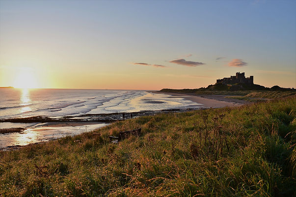 Photograph of Bamburgh beach, Northumberland at sunset, with the castle in the background. Photo courtesy of Bruce Edwards via Unsplash.