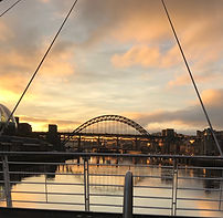 A view from the Millenium Bridge, Newcastle upon Tyne out across the Tyne river at sunset. To the left is the Sage Gateshead, to this right the Newcasle Quayside, and straightahead the Tyne Bridge which is reflected in the water below.