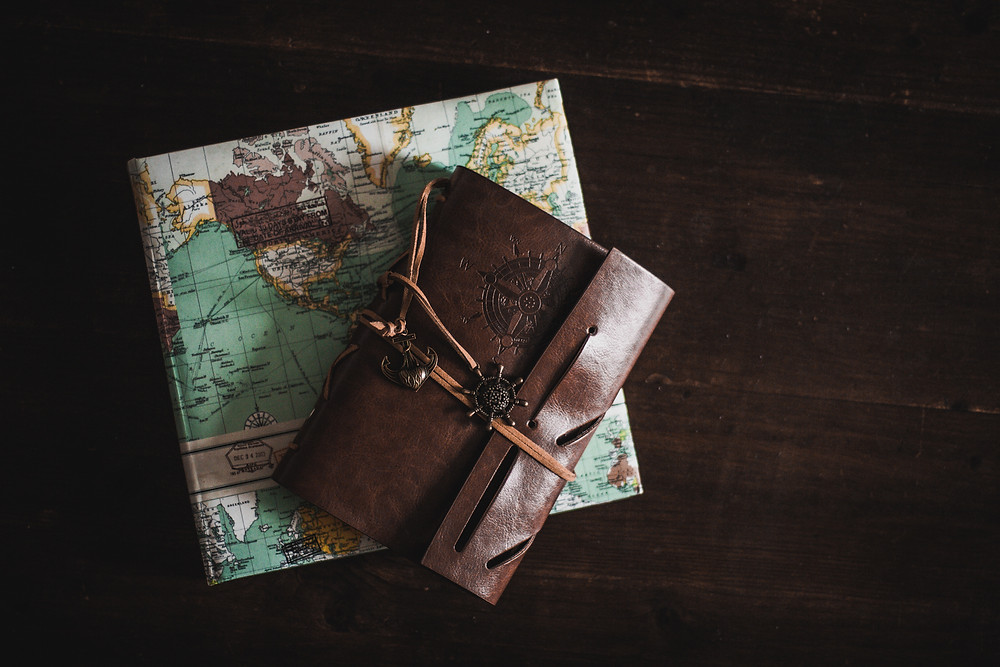 Photo (courtesy of Kira Auf Der Heide via Unsplash) of a brown leather journal and coloured map album, both on top of a dark wooden desk.