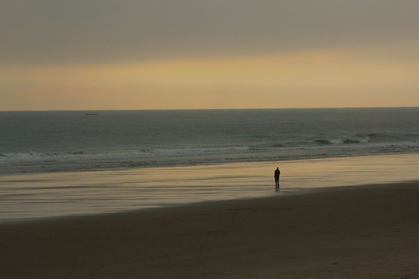 Photograph of a silhouetted figure looking out to see on the beach at Tynemouth, North East England.