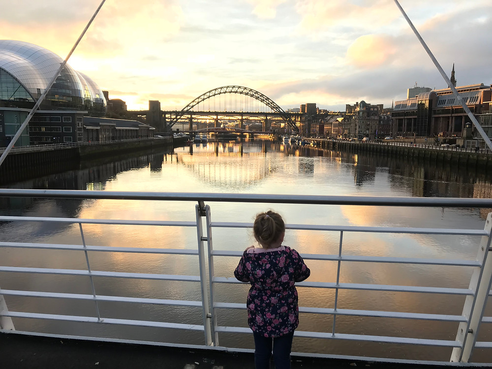 Photograph of a little girl in a pink and blue flowered coat, standing on a bridge looking out over the River Tyne and Newcastle Quayside as the sun begins to set in the sky. Photograph property of Ceryn Rowntree.