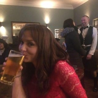 Photograph of a woman - Ceryn Rowntree - drinking a pint of cider in a pub with friends.