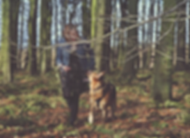 Ceryn Rowntree, a far skinned brunette in her 30s, walks through a forest with her dog Kali, a black and tan German Shepherd, to her left. There are tall trees around them and a large bare horizontal tree branch to the front of the image.