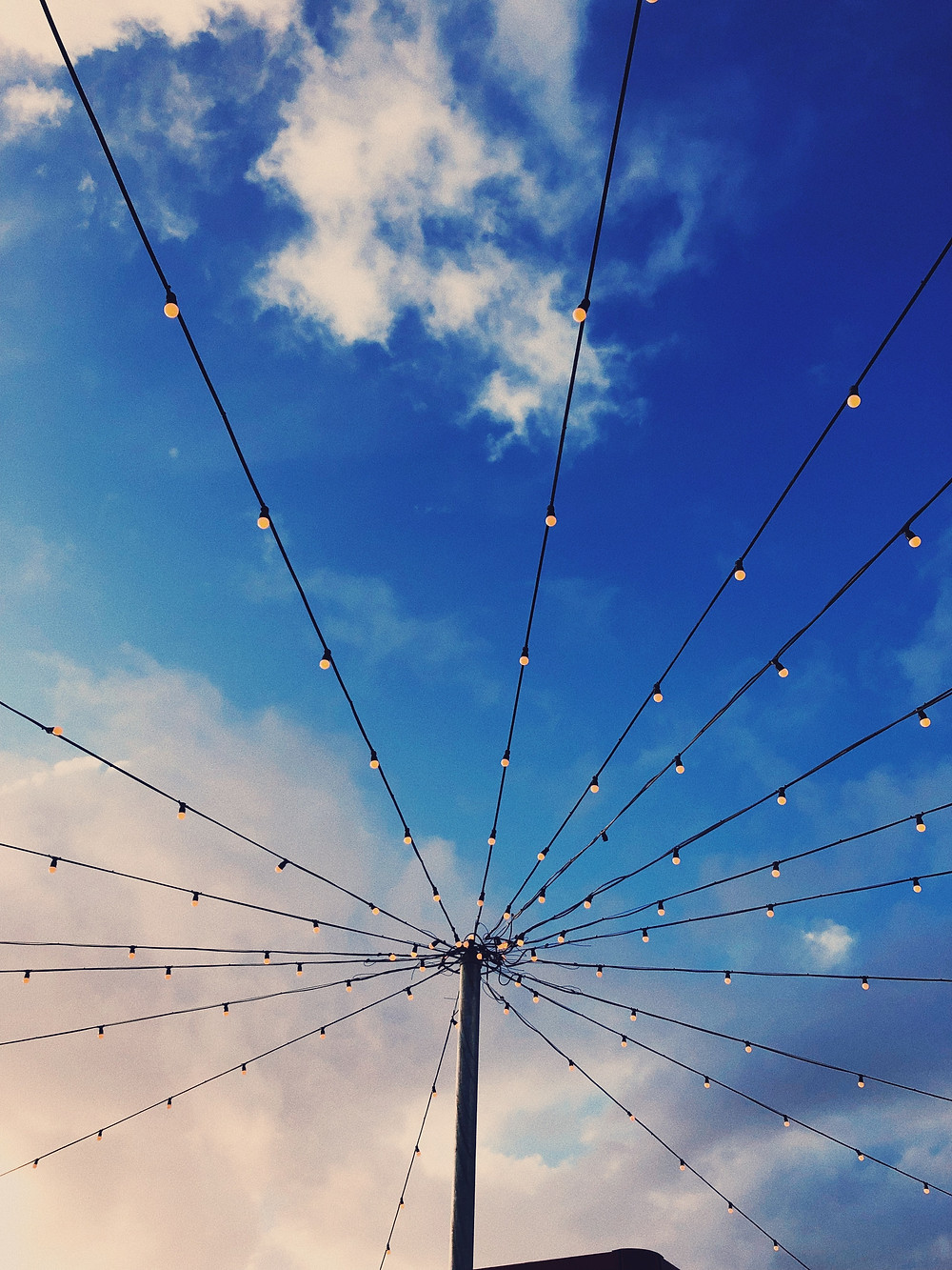 A series of strings containing fairy lights spread out as spokes from a central pole, with a blue cloudy sky behind them. Image is courtesy of Bruno Figueiredo on Unsplash