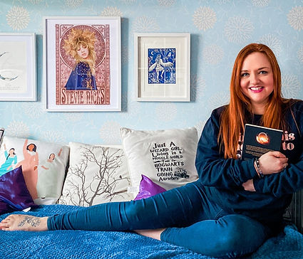 Photograph of Ceryn Rowntree, a white woman with long red hair, sitting on a blue day bed with her legs outstretched and holding a book. Behind her are cushions and three framed images. Photograph is by Becky Wright photography.