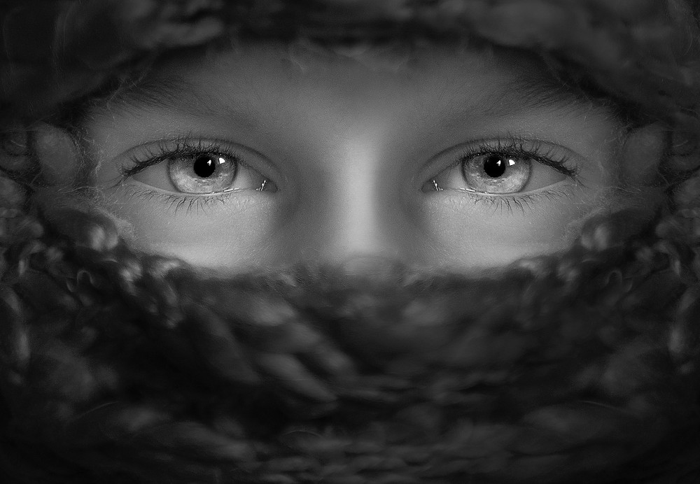 Grayscale photo showing a light skinned woman's eyes staring out of a circular space surrounded by wool. Photo by Kat J on Unsplash.