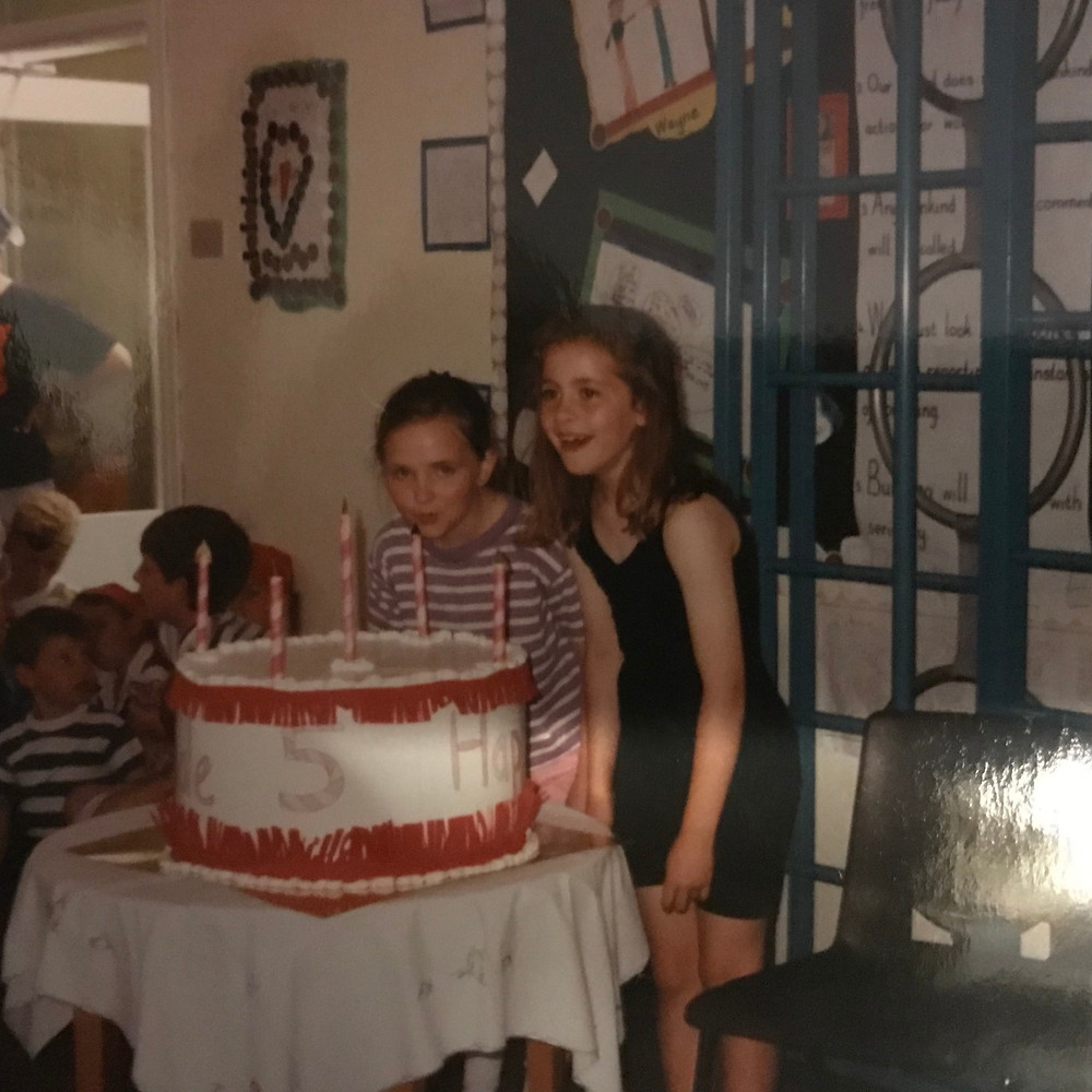 Photograph of two young girls pretending to blow out candles on a large fake birthday cake in a school hall. Ceryn is the girl on the right.