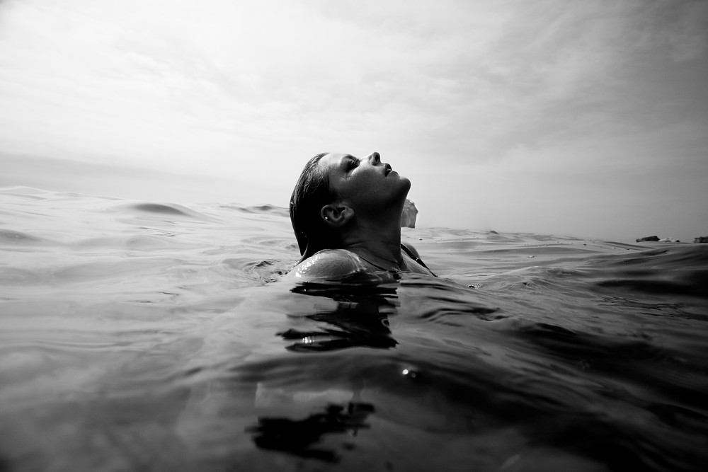 Black and white photograph of a woman emerging from the water, her head and shoulders visible above the waves. Photo courtesy of Jeremy Bishop on Unsplash.