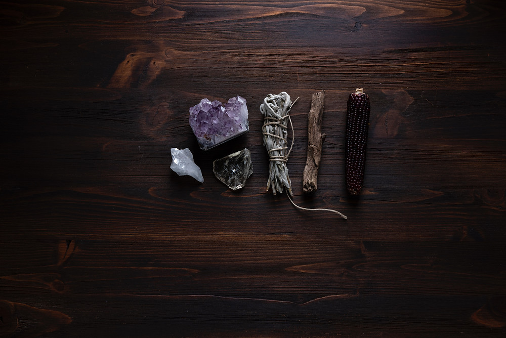 Some of the tools of a soul worker; a number of crystals lie on a dark wooden surface along with a sage smudge stick, a wooden stick or wand and a large piece of red corn. The image is courtesy of Joanna Kosinska on Unsplash.