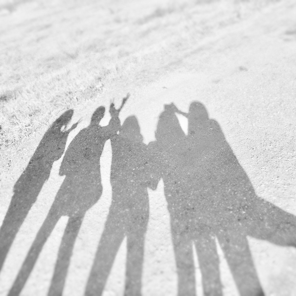 Photograph showing the shadows of a group of five people standing together and apparently posing for a photograph against a light coloured floor. Photo by Merritt Brown on Unsplash