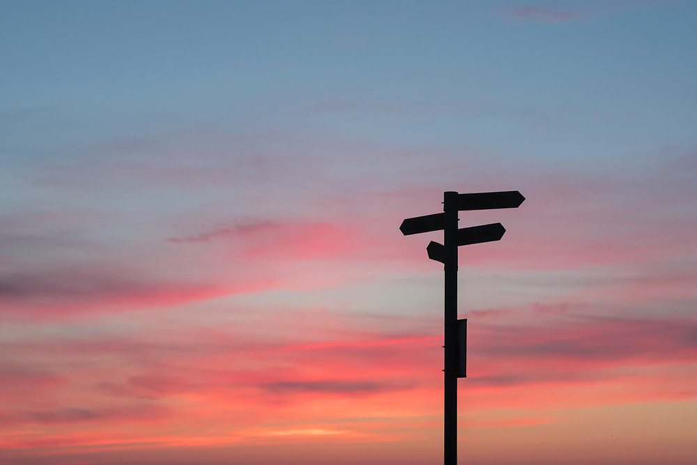 Signpost against a colourful sky as the sunsets. Photo courtesy of Javier Allegue via Unsplash.
