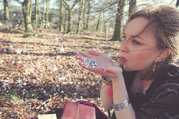 Image shows Ceryn Rowntree blowing silver stars from her hands against the backdrop of an autumnal forest. Image by Laura Pearman.