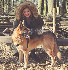 Ceryn Rownree - a fair skinned brunette in a khaki colored winter coat witha large furtrimmed hood sits on a wooden bench in a forest, with her dog Kali, a black and tan German Shepherd, standing in front of her