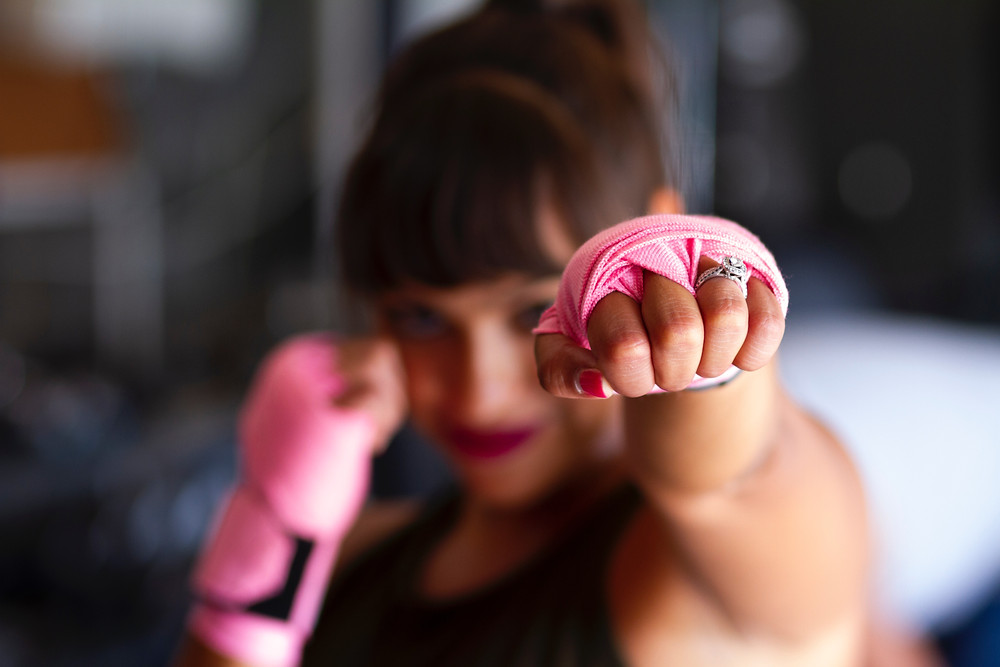 Photograph (courtesy of Sarah Cervantes via Unsplash) of a woman with dark hair and lipstick and bright pink nails. Her hands are wrapped in pink gloves or tape and she has her right hand up to guard her face in a boxing pose while her left fist is outstretched towards the camera.