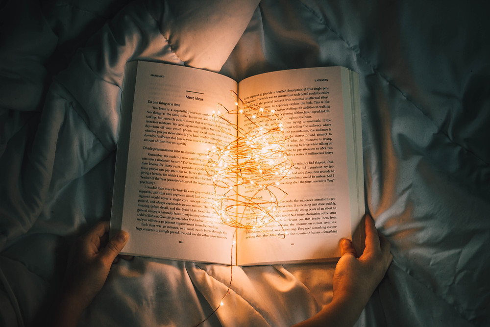 Photograph of a book open on a bed, the room around it is dark but illuminated fairy lights sit in the centre of the book. Photo courtesy of Unsplash.