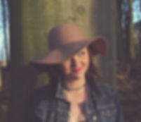 Cery Rowntree, a fair skinned brunete n her thirties stands in front of a tall, scarred tree trunk in a wood. She is wearing a dark blue denim jacket and a number of necklaces, with a wide-brimmed, tan-coloured hat on her head, and is loking to the left while smiling.