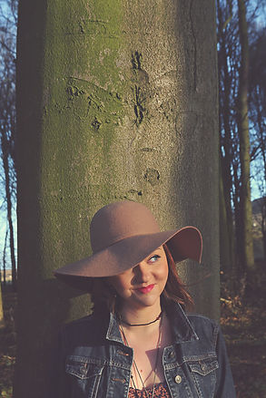 Cery Rowntre, a fair-skinned bunette in her 30s standswith her back to a tall, scarred tree trunk in a forest. She wears a blue denim jacket, a number of necklaces and a wide-brimmed tan felt hat. She looks to the left with a smile on her face