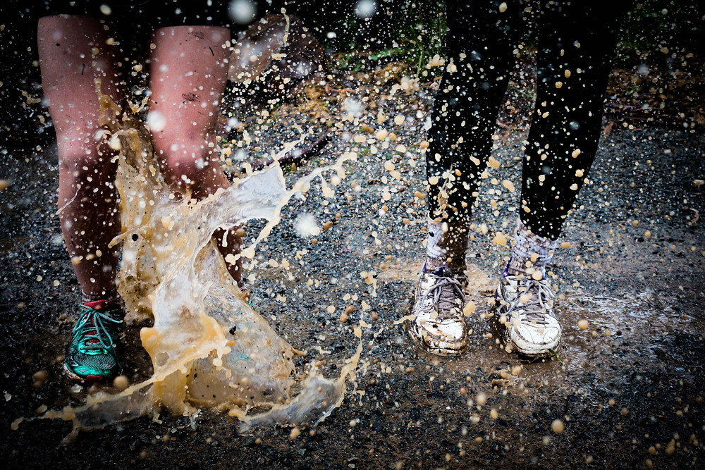 Photograph of two pairs of legs splashing in a muddy puddle. Photo courtesy of Josh Calabrese on Unsplash