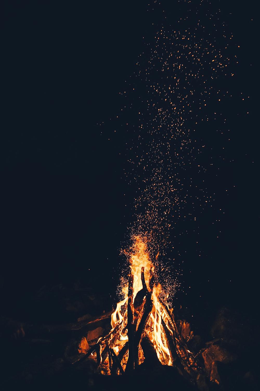 Photograph of an orange bonfire burning against a black sky, sparks floating upwards. Photo courtesy of Toa Heftiba on Unsplash.
