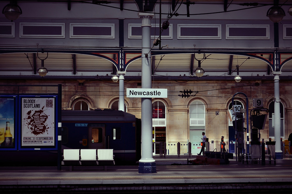 Photo of a stationary train in Newcastle Central railway station. Photograph courtesy of Devon Saccente via Unsplash.