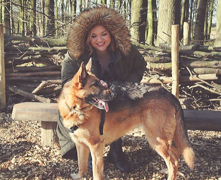 Photograph of Ceryn Rowntree sitting on a bench in the woods wearing a large green parka coat. In front of her is her dog Kali, a tan and black German Shepherd. Photograph is by Laura Pearman photography.