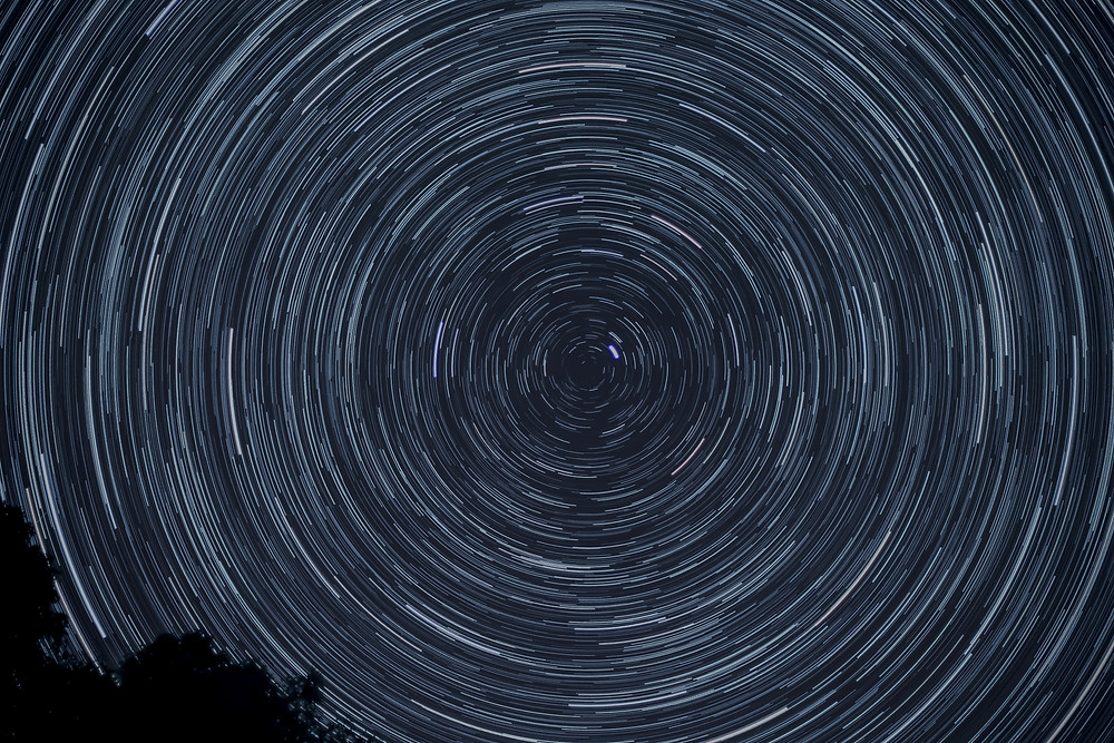 A time lapse photo of the stars, spiralling in a dark sky. Photo courtesy of Patrick McMahon via unsplash