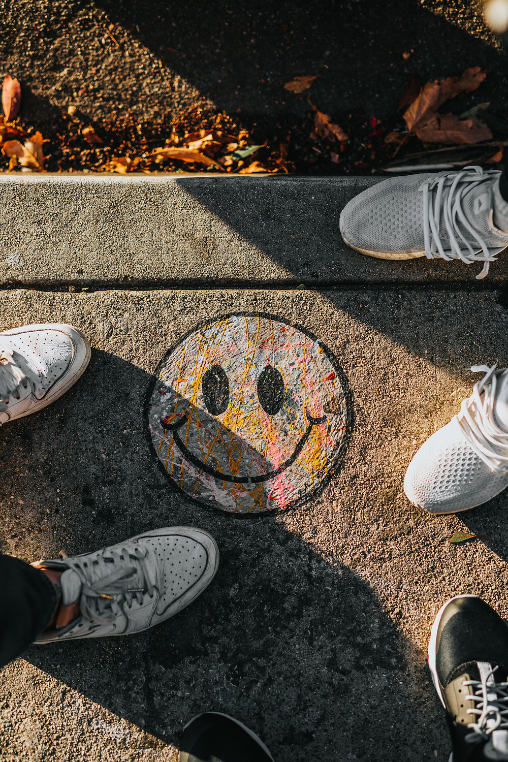 "A drawing of a smiley ""acid"" face on a cement block surrounded by earth and brown leaves. Two people stand on the block wearing white trainers, with one on each side of the face. Photo is by Nathan Dumlao on Unsplash."