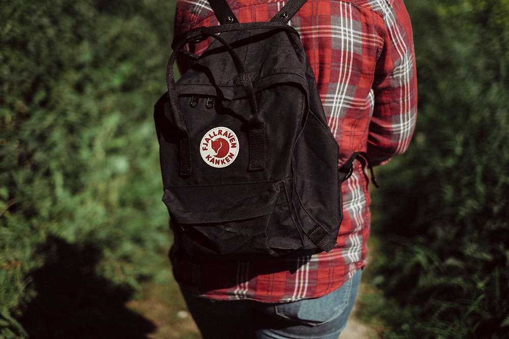 Photograph of a person with their back to the camera/ The person wears a red checked shirt and jeans, with a black backpack on their shoulders. In front of them are high green plants. Photo by Mitchell Orr courtesy of Unsplash.