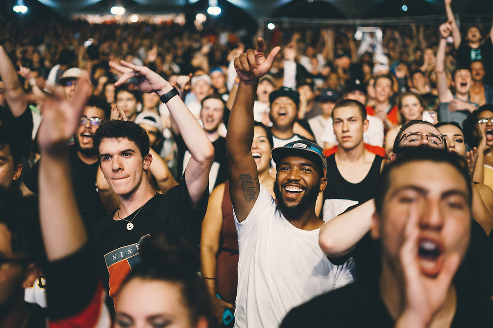 A crowd comprised predominantly of young men cheer and shout with their hand in the air. Photo by Nicholas Green on Unsplash