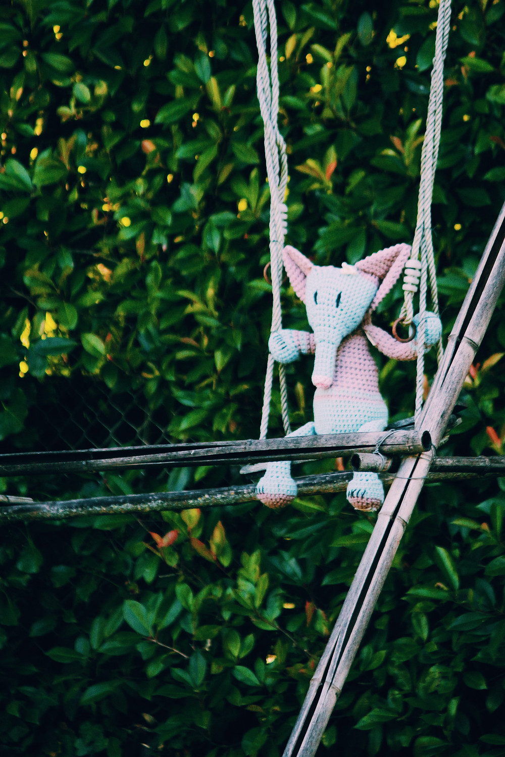 A knitted elephant sits on a wooden swing, with green trees in the background. Photo by Emeric Deroubaix on Unsplash.