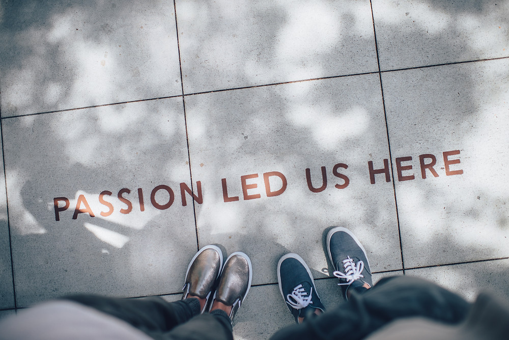 """A photograph pointing down at two pairs of feet on a pavement with the words """"passion led us here"""" painted in front of them. Photograph courtesy of Ian Schneider on Unsplash"""