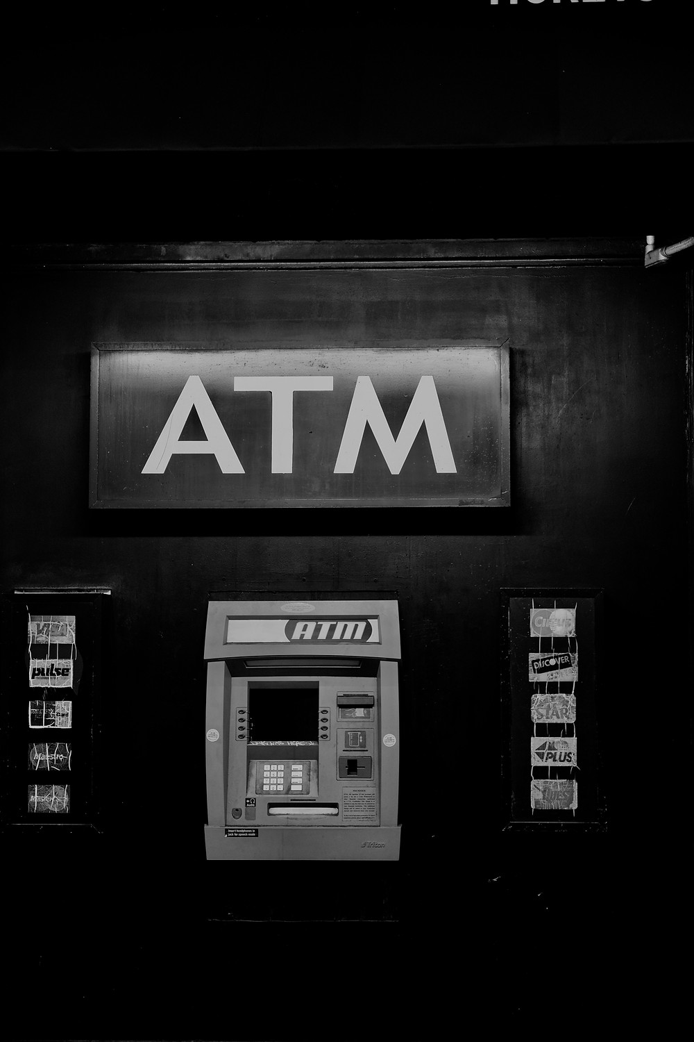 Black and white photograph of an unbranded ATM machine. Photo by Johny vino on Unsplash.
