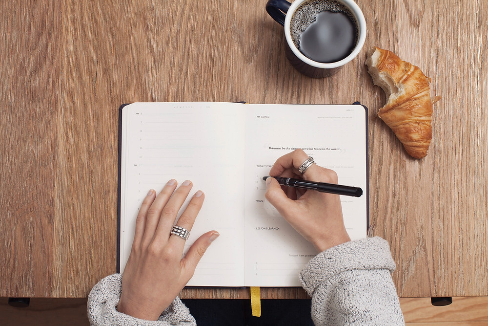 A person writes a list in a journal. On the table next to their book are a croissant and a cup of coffee. Photo by Cathryn Lavery on Unsplash.