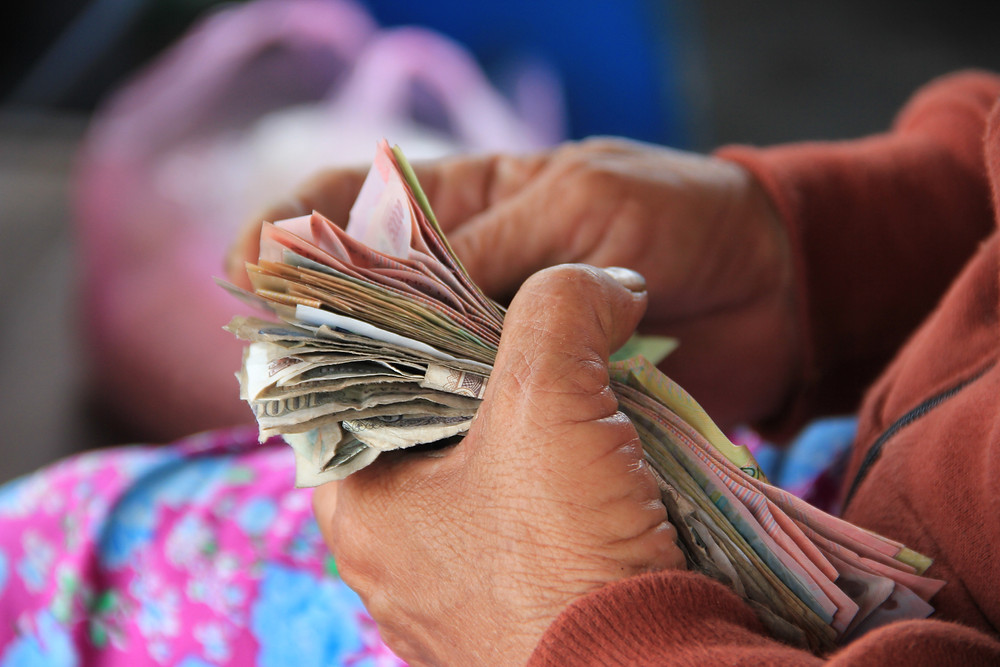 A photograph of a pair of female hands holding a bundle of notes. Photo by Niels Steeman on Unsplash.