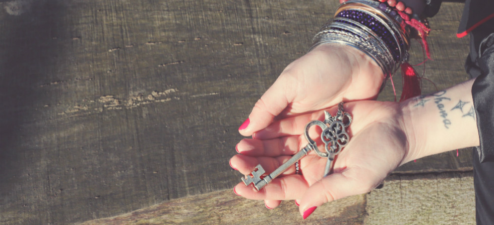 A pair of female hands are outstretched holding two silver keys over a dark piece of wood. The hands belong to Ceryn Rowntree, Soul-Centered Counsellor.