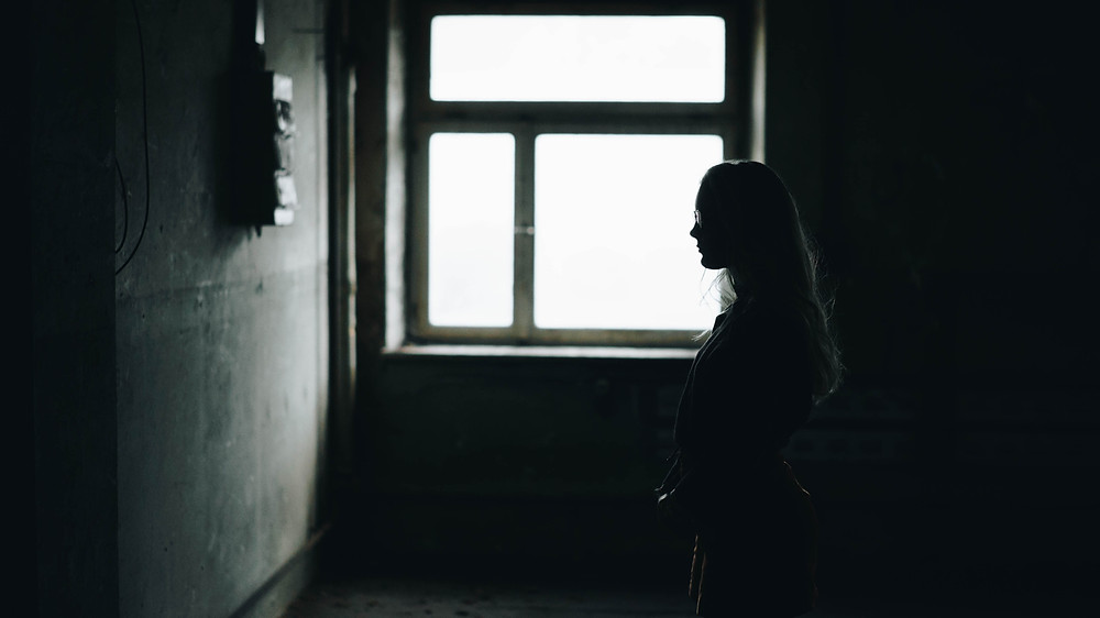 Photo (courtesy of Alex Ronsdorf via Unsplash) of a silhouetted woman looking at a wall with a window behind her.