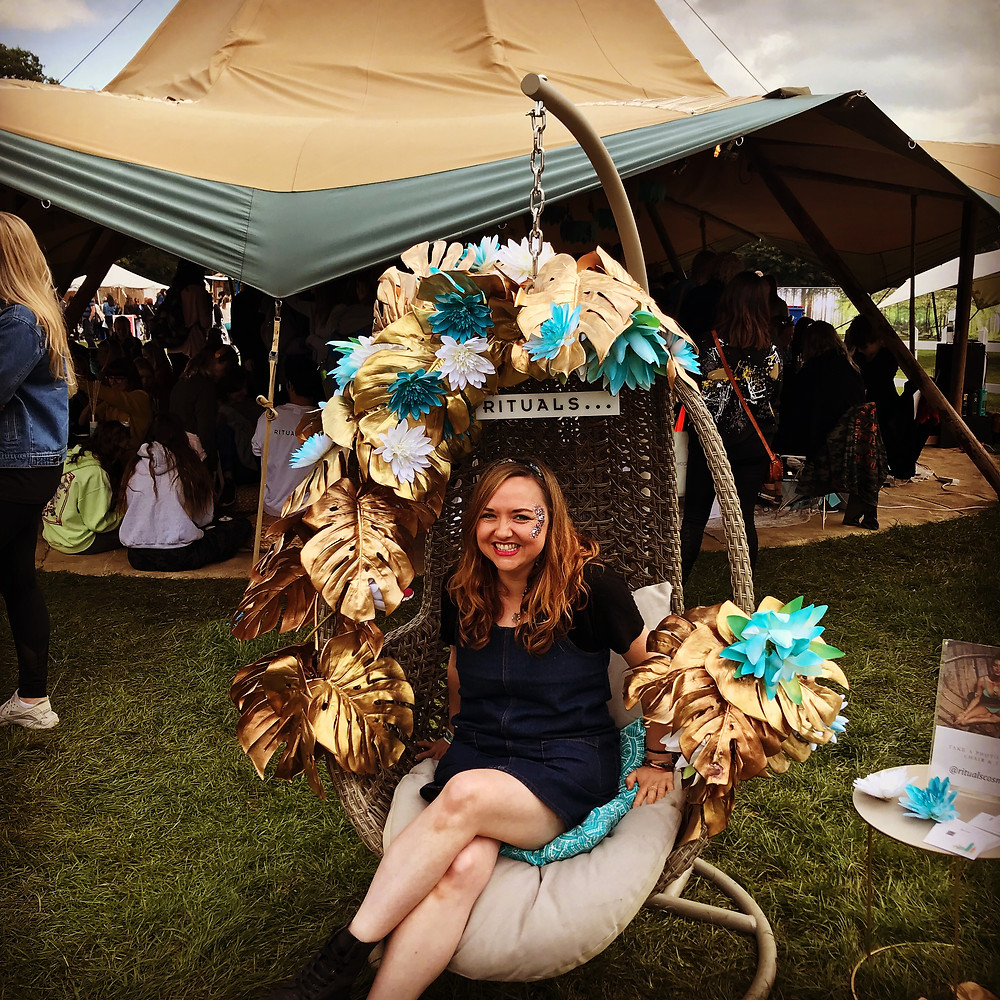 Photograph of Ceryn Rowntree sitting inside a swinging chair surrounded by blue and gold flowers.