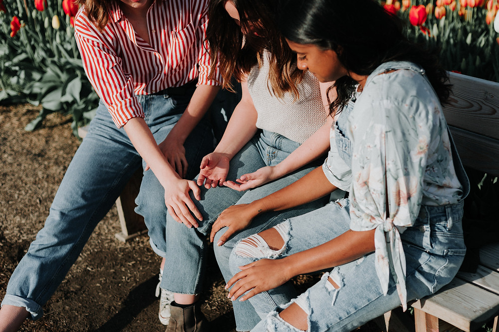 Three women sit on a bench, resting their hands on the central woman's legs. Photo by Priscilla Du Preez on Unsplash