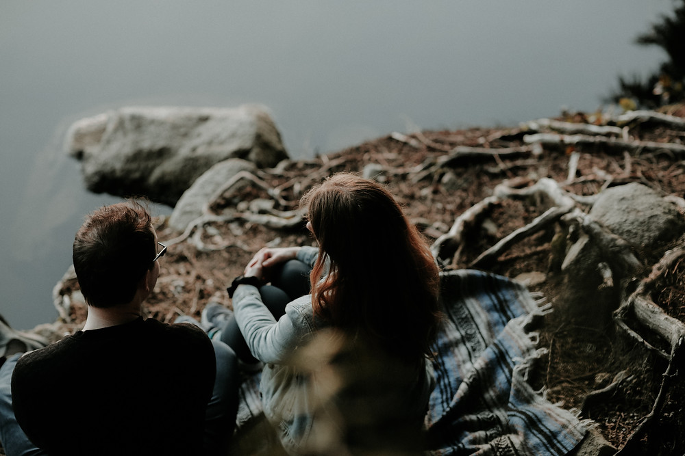 A man and woman sit on an earth floor at the edge of some water. They are facing away from the camera. The man is white with short, dark hair and wears a dark sweatshirt while the woman is also white with long dark hair and wears a denim jacket. They sit on a rug with their backs against a crop of rocks.Photo by Priscilla Du Preez on Unsplash