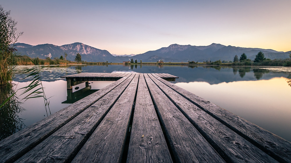 Image of a wooden jetty stretching out over a lake, with mountains in the background. Photo by Mario Doblemann, courtesy of Unsplash.