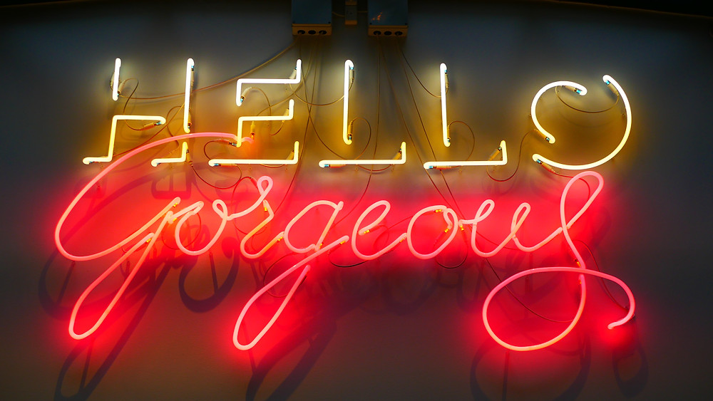 "Photo of a fluorescent sign which reads ""hello gorgeous"", with the words in white and red respectively. Photo by Karine Germain on Unsplash."
