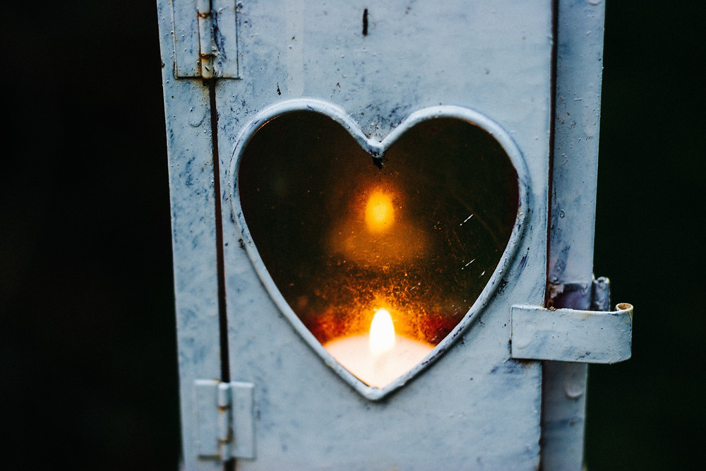 Photograph of a lit candle visible through the heart-shaped window of a light coloured medal box. Photo byCathal Mac an BheathaonUnsplash