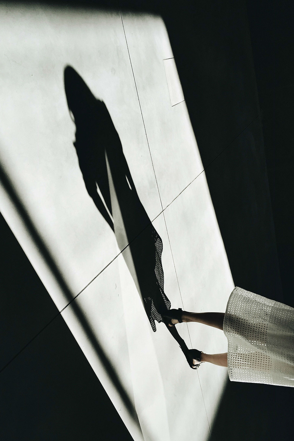 Photo of the shadow of a woman on a light coloured floor, with the woman's legs, feet and white skirt visible to the right of the image. Photograph courtesy of Martino Pietropoli via Unsplash.