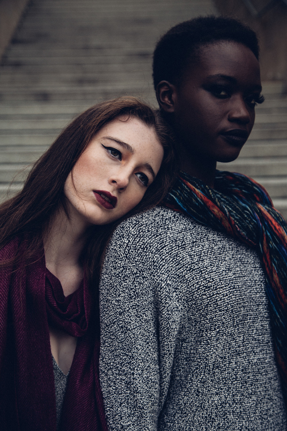 Photograph of two women leaning on one another against a grey background. To the right is a pale skinned woman with red hair and dark eyeliner and lipstick. She wears a black top and leans her head on the shoulder of the woman to the right of the image. The second figure has dark skin, thick eyelashes and short, dark hair. She wears a grey sweatshirt and a multicoloured scarf.  Photo by Shamim Nakhaei on Unsplash