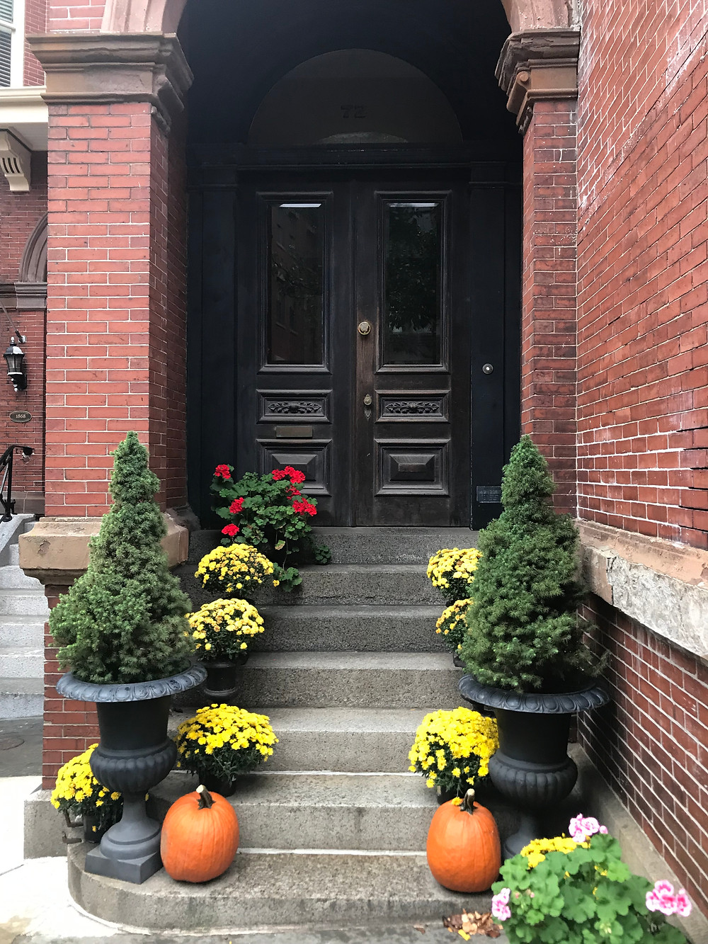 A red bricked house with a black door and autumnal flowers and pumpkins on the step.