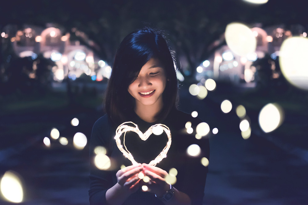 Dark haired woman holds a heart made out of illuminated white wire. She wears a black tshirt and has long, dark hair hanging loose. Around her are a number of white lights, with a blurred out illuminated scene behind her. Photo by Bart LaRue on Unsplash