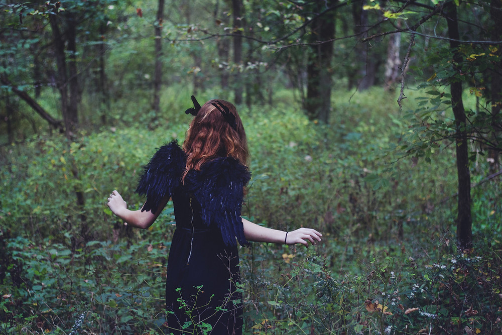 A photograph of a pale-skinned woman with loose long dark hair walking in an overgrown wood. The woman wears a black dress with what looks like black wings over her shoulders. Photo is courtesy of Alex Grodkiewicz and shared via Unsplash.